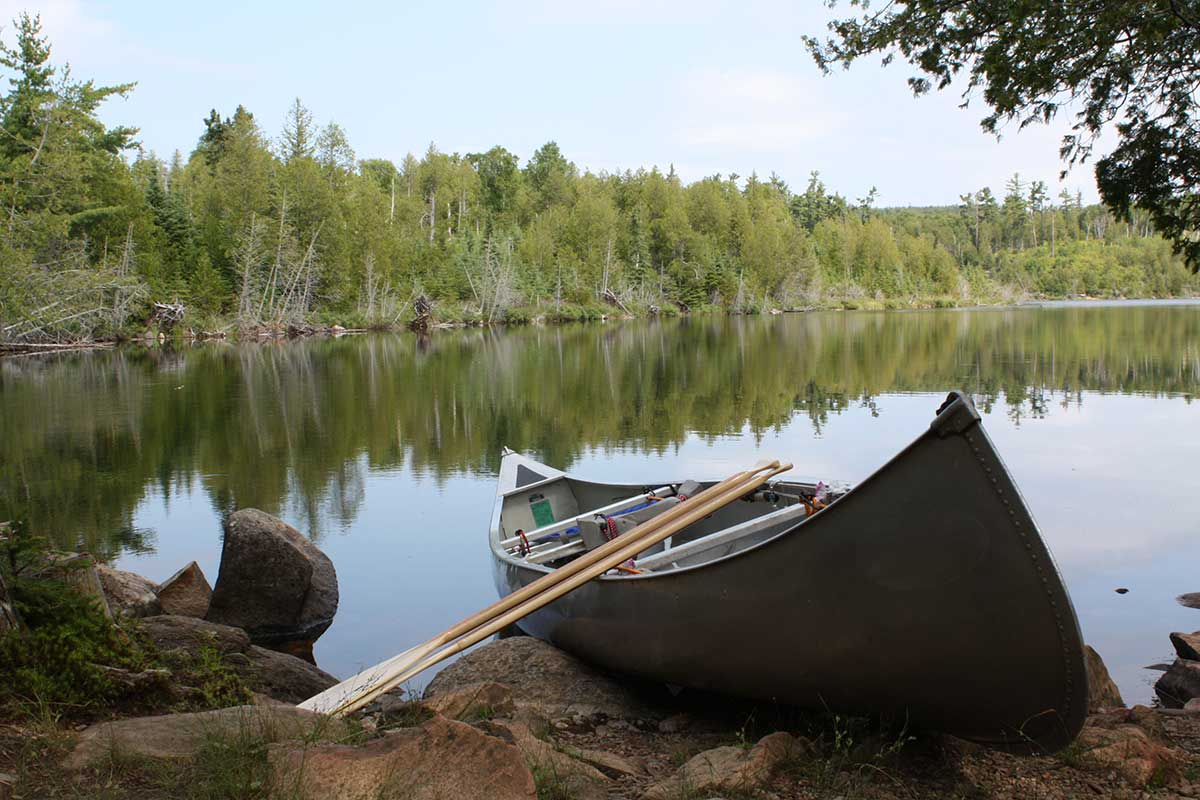 image of a canoe on the shore of a lake
